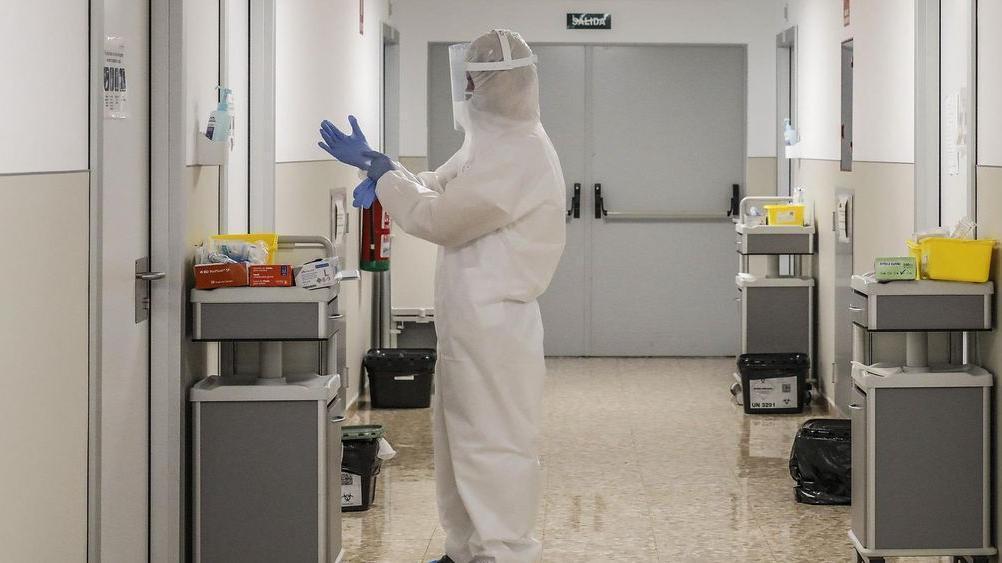 Un sanitario se prepara con el EPI en un hospital valenciano.
