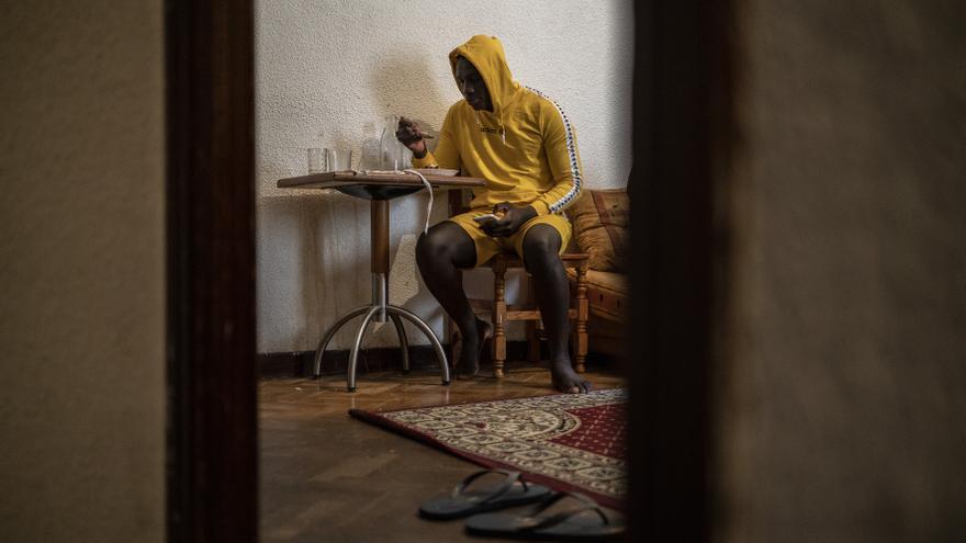Un joven mantero come arroz con pollo en el salón de su casa.
