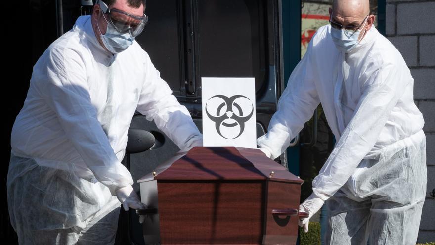 Trabajadores de una funeraria sacan un ataúd de una víctima de coronavirus en Gilly, Bélgica el 26 de marzo.