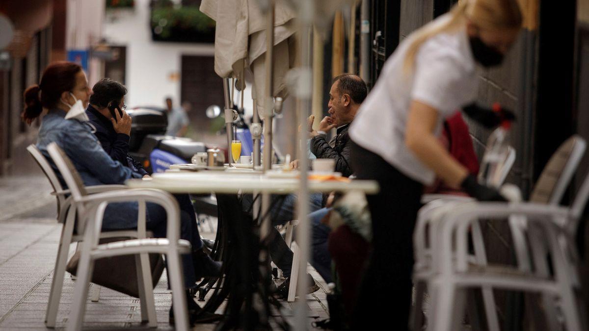 Una camarera de una cafetería de Santa Cruz de Tenerife limpia una mesa mientras varios clientes toman sus consumiciones en la terraza