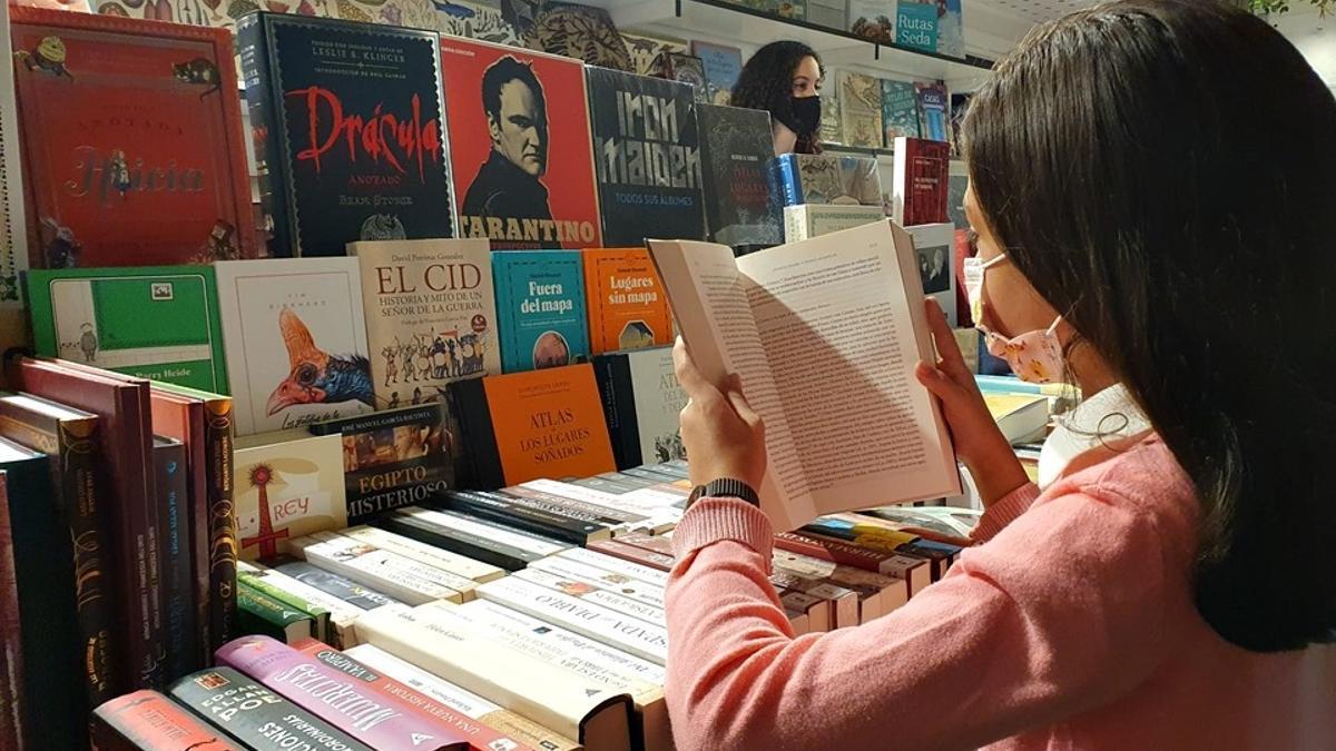 Una joven hojea un libro en la Feria del Libro de Mérida 2020