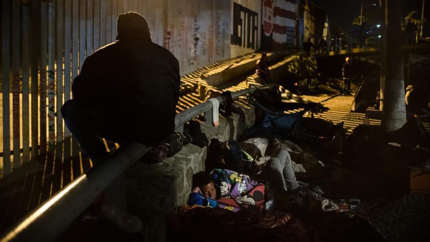 Integrantes de la caravana migrante descansan frente al muro con EEUU.