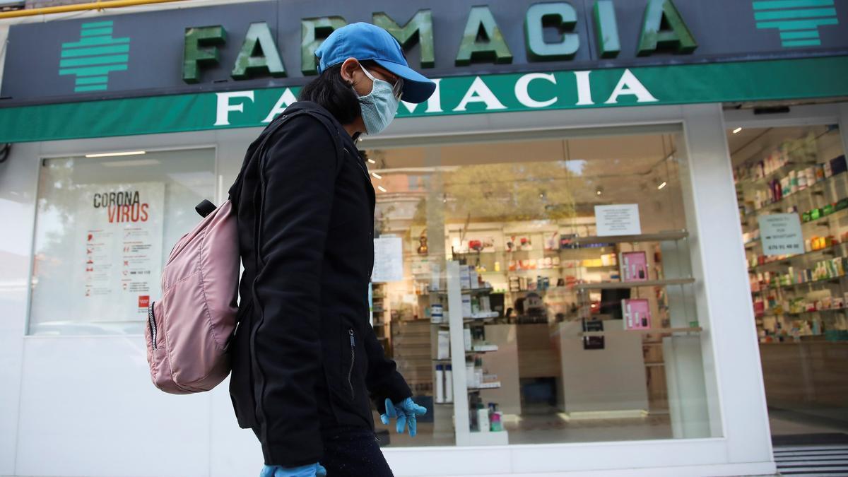 Una viandante, protegida con guantes y mascarilla, pasa por delante de una farmacia