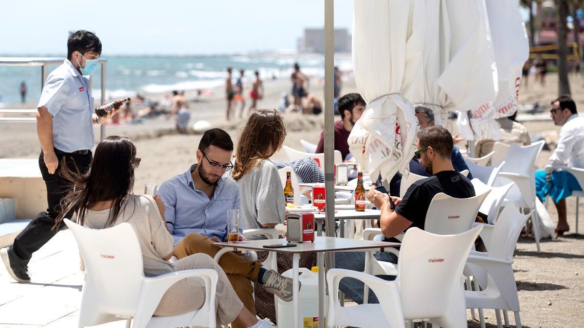 Varias personas disfrutan del buen tiempo en los chiringuitos de la playa de La Misericordia de Málaga este sábado 1 de mayo. EFE/Daniel Pérez