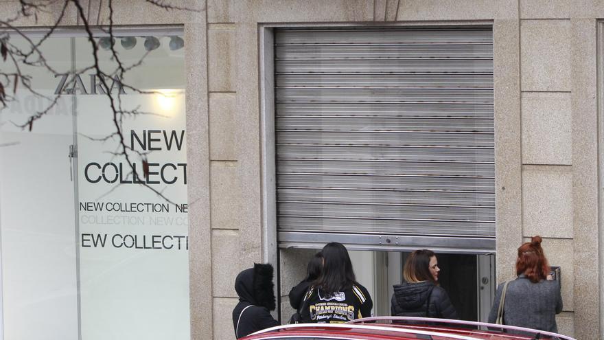 Trabajadoras del Zara de Ferrol bajan la persiana de la tienda que cierra definitivamente sus puertas.