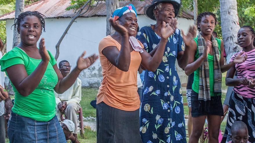 """Mujeres cantan en reunión informativa sobre el proyecto Île-à-vache 'Cantando se lucha mejo'r: """"Tenemos patatas, tenemos pescado, no necesitamos este proyecto""""./ I. F."""