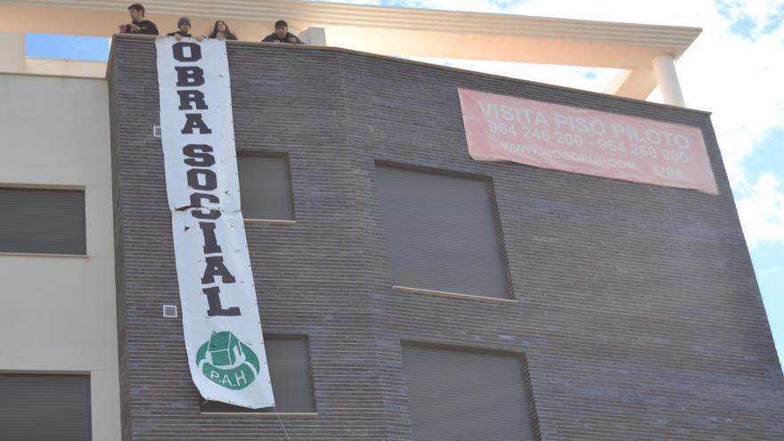 Activistas de la PAH despliegan una pancarta desde la azotea del edificio ocupado en Castellón.