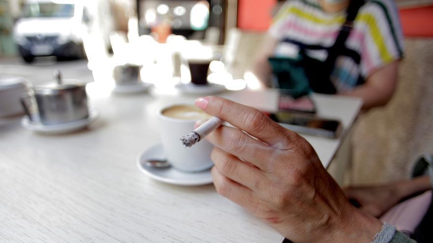 Una mujer fuma, este jueves, en la terraza de un bar de A Coruña. EFE/ CABALAR