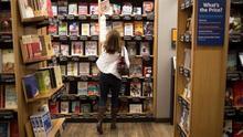 Una mujer alcanza un libro en una estantería de una librería.