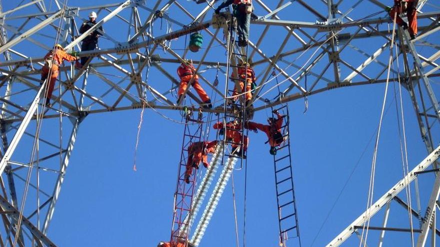 Empleados de Abengoa levantan una torre electrica en Chile