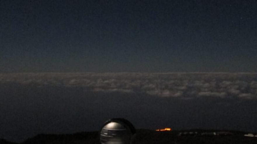 En la imagen, tomada en torno a las 02.00 horas de este viernes, se aprecia, al fondo, la iluminación del futuro Centro de Visitantes, con la cupula del Gran Telescopio Canarias en primer término..