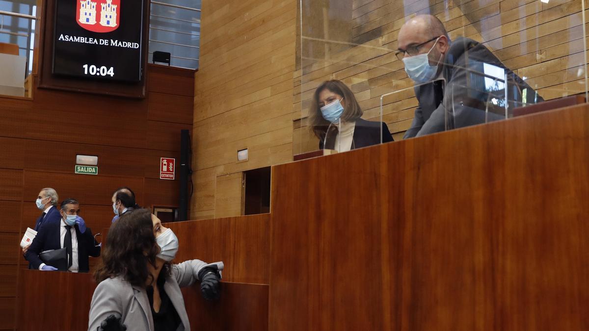 El presidente de la mesa, Juan Trinidad, charla con la presidenta de la Asamblea de Madrid Isabel Díaz Ayuso.