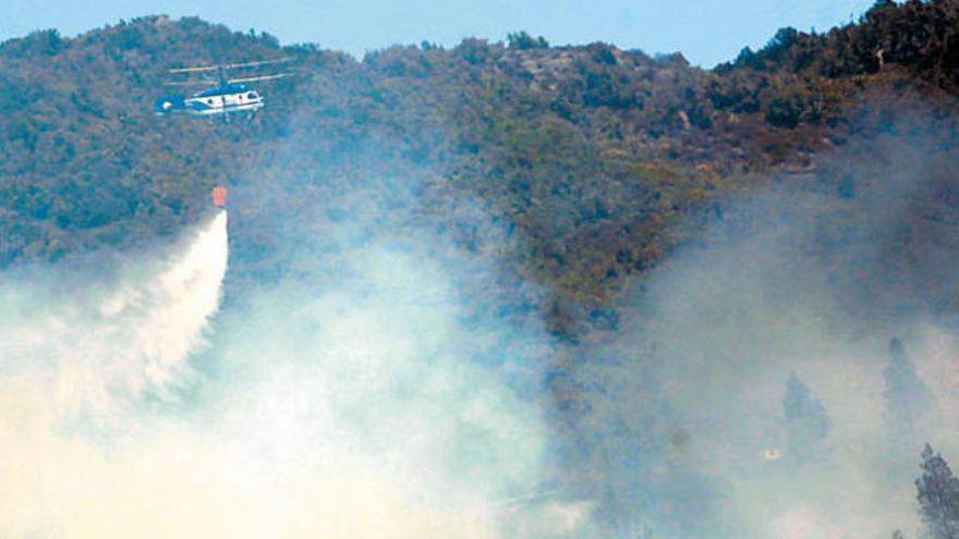 Un helicóptero descarga agua sobre el Garajonay. (ACFI PRESS)