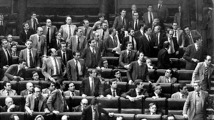 Un grupo de parlamentarios mira hacia la puerta durante el intento de golpe de estado del 23F