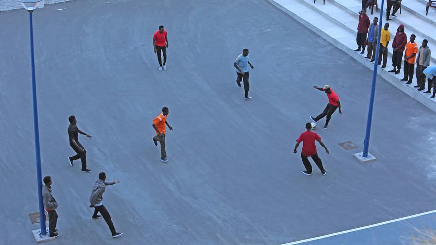 U gnrupo de personas que llegó a Gran Canaria juegan al fútbol en un centro de El Polvorín cedido por el Ayuntamiento de Las Palmas de Gran Canaria a Cáritas.