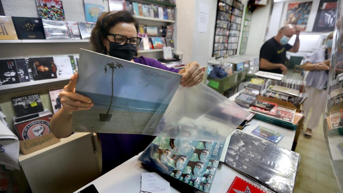 Carmen Arnal, una de las fundadoras y gestoras de Oldies, enfunda un vinilo antes de guardarlo