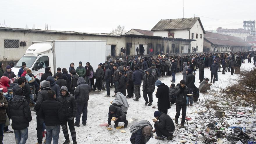 Personas hacen cola para la distribución de raciones de comida y mantas fuera de un almacén de la estación abandonada, usada como refugio por los demandantes de asilo en Belgrado, Serbia, el 5 de enero de 2017.