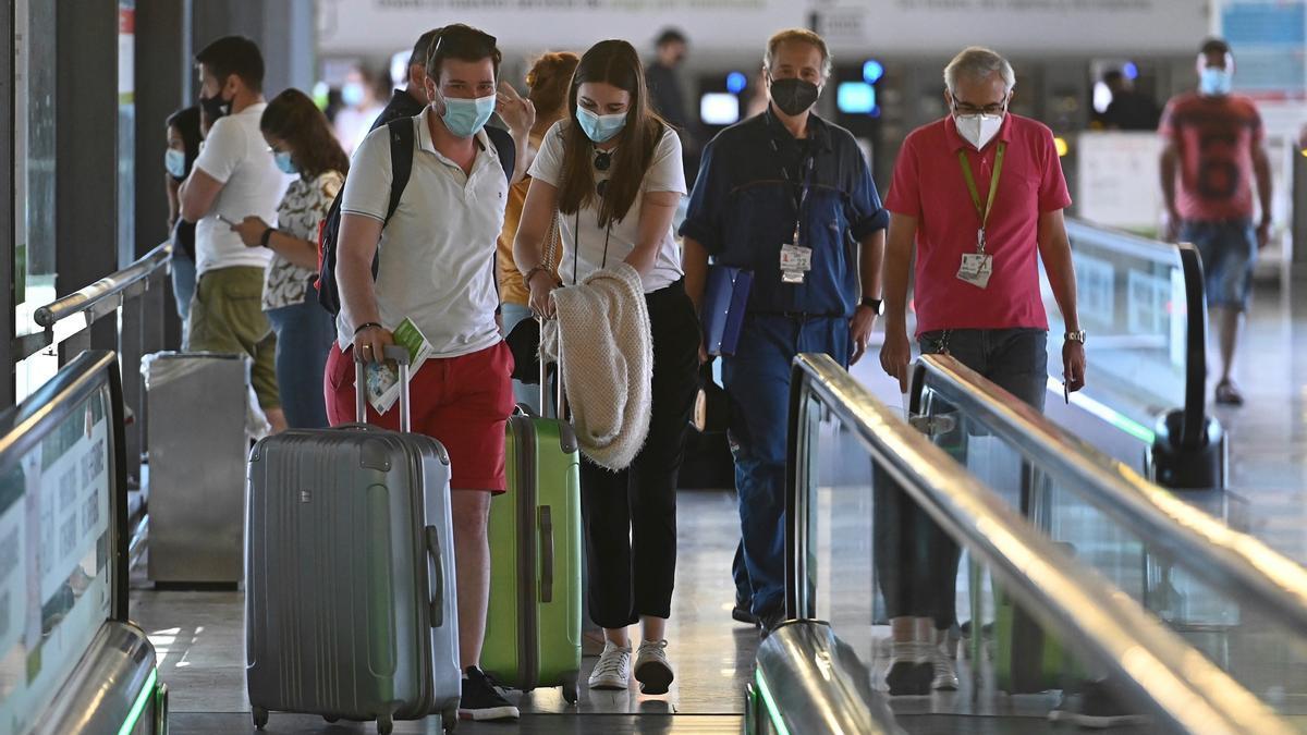 Varios turistas caminan por la terminal 4 del aeropuerto Adolfo Suárez Madrid Barajas, en una fotografía de archivo. EFE/Fernando Villar