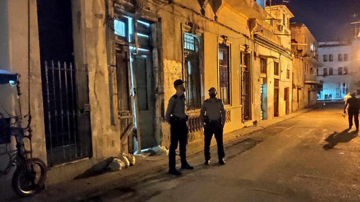 Dos policías permanecen afuera de la casa donde se encontraban los disidentes en huelga de hambre y sed hoy, en la barriada de San Isidro, en La Habana (Cuba).