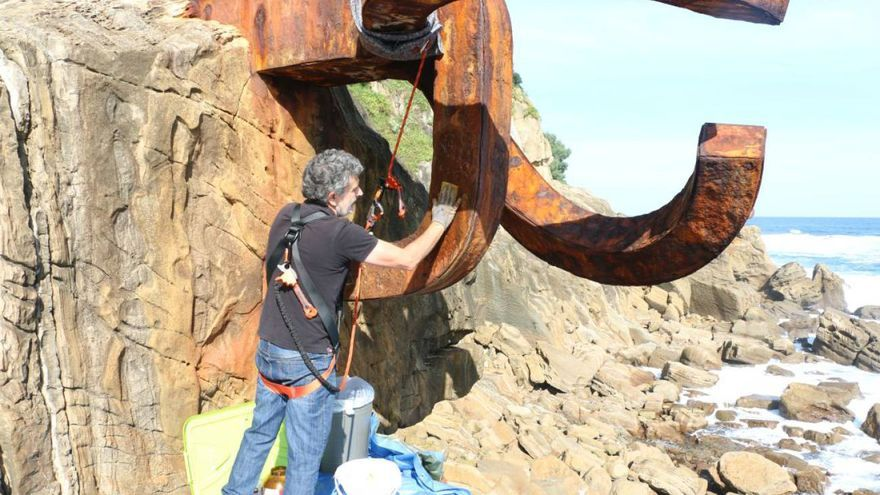 Expertos en limpieza del Museo Chillida Leku limpian los lazos amarilos pintados en el Peine del Viento