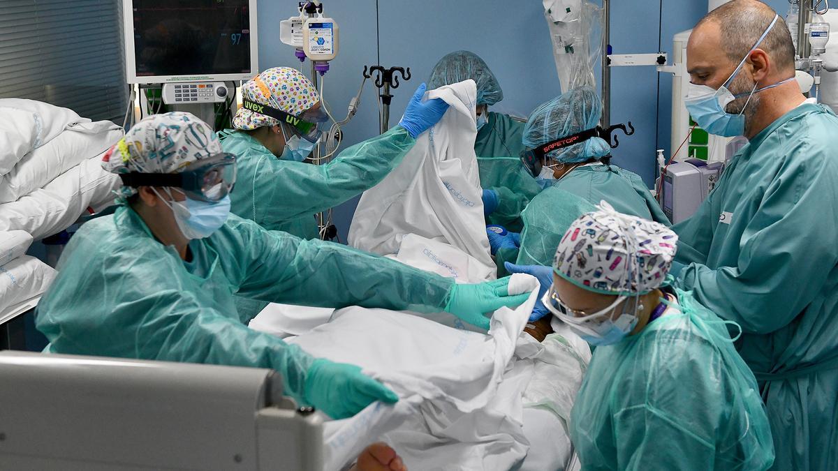 Seis sanitarios realizan el cambio de postura de un paciente de coronavirus en la UCI del Hospital Sant Pau de Barcelona