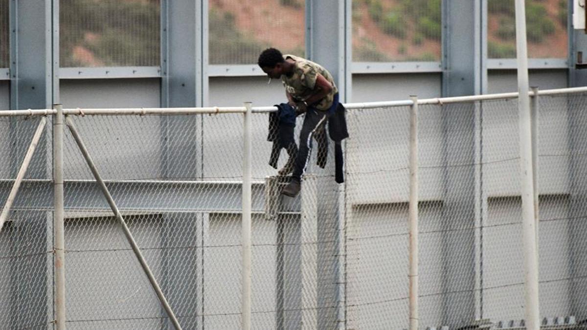 Un inmigrante encaramado al vallado intenta entrar en territorio español a través de la valla fronteriza que separa Ceuta de Marruecos, este martes.