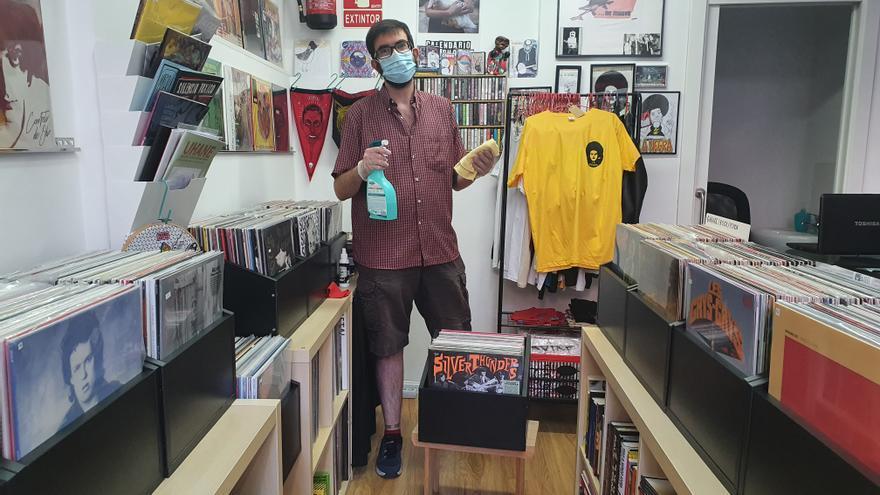 Mario, de la tienda de discos La Negra, dándole al desinfectante.