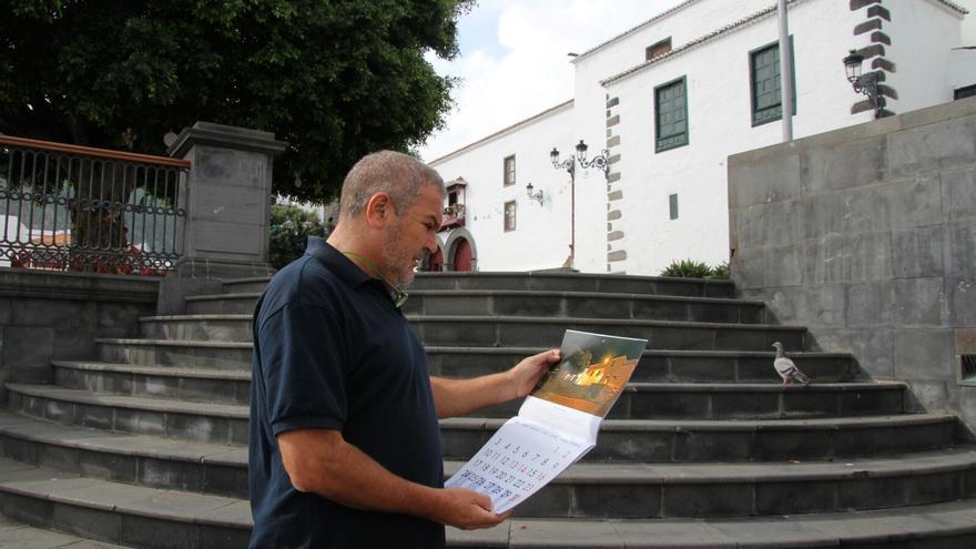 José Ayut muestra el calendario que está ilustrado con sus imágenes.