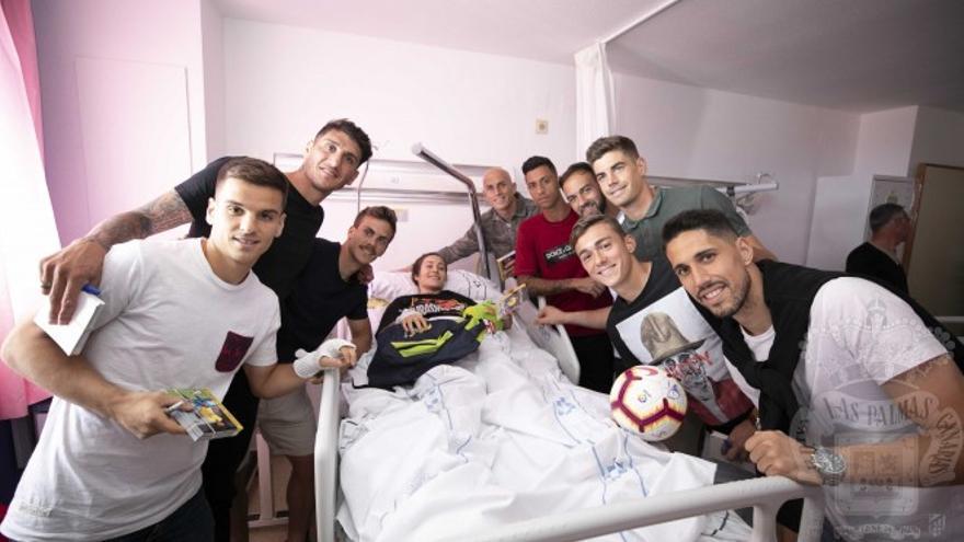 Varios jugadores de la UD Las Palmas posan con uno de los menores internos en el Materno Infantil.