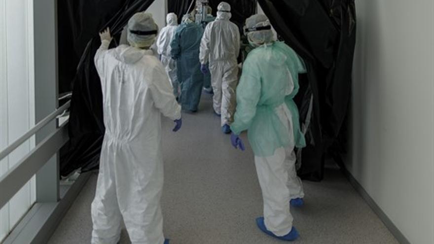 Personal sanitario totalmente protegido trasladan a un paciente ingresado en la Unidad de Cuidados Intensivos del Hospital Infanta Sofía en San Sebastián de los Reyes (Madrid)