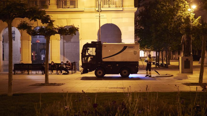 Archivo - Unos jovenes sentados mientras un trabajador de limpieza trabaja en la Plaza del Castillo alrededor de la media noche