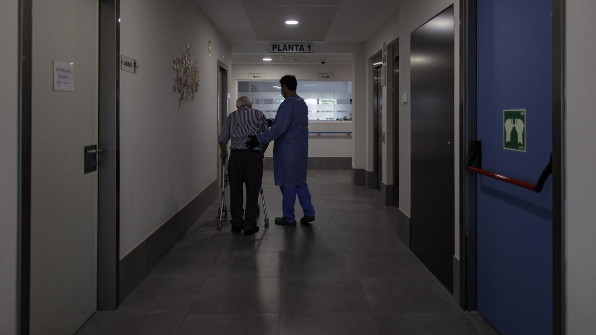 Un trabajador atiende a un anciano en una residencia de mayores.