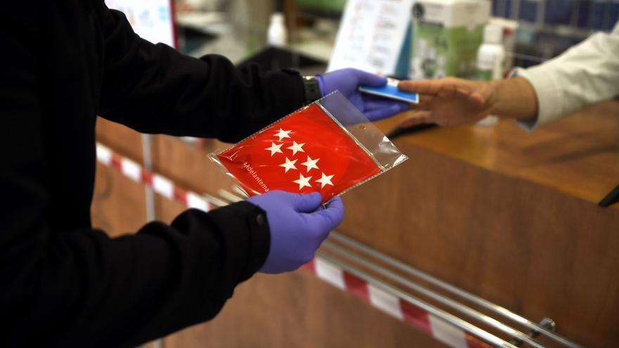 Un cliente coge una de las mascarillas que reparte la Comunidad de Madrid en las farmacias presentando la tarjeta sanitaria.
