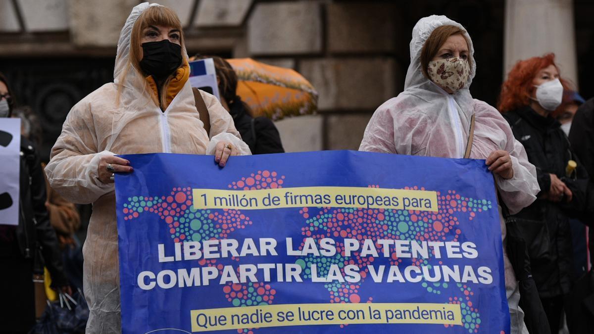 Dos mujeres vestidas con un Equipo de Protección Individual (EPI) participan en una manifestación que reclama la liberación de las patentes de las vacunas para el Covid-19, a 7 de abril de 2021, en Valencia, Comunidad Valenciana (España). Esta protesta se enmarca en la iniciativa europea Right2Cure y ha sido convocada por la Plataforma valenciana per la Salut Pública.