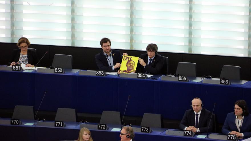 Puigdemont y Comín, con una foto de Junqueras en su escaño del Europarlamento
