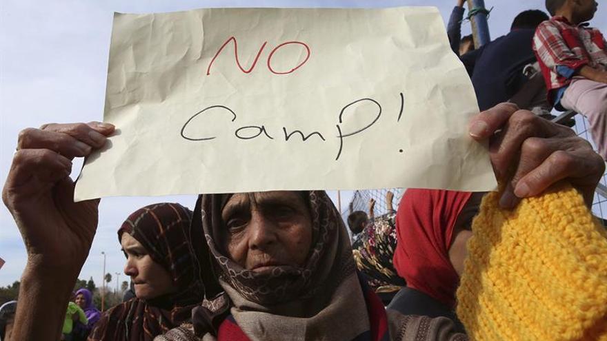 Una mujer sostiene un papel durante una manifestación contra la situación de los refugiados en un asentamiento improvisado en Atenas.