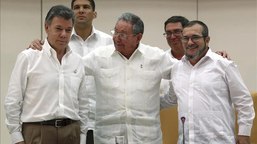 Raúl Castro, en el centro, abraza al presidente Santos y al comandante general de las FARC, Timoleón Jiménez./ EFE