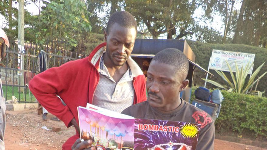 Dos mototaxistas leen Bombastic sobre su boda-boda / Fotografía: Henry Wasswa