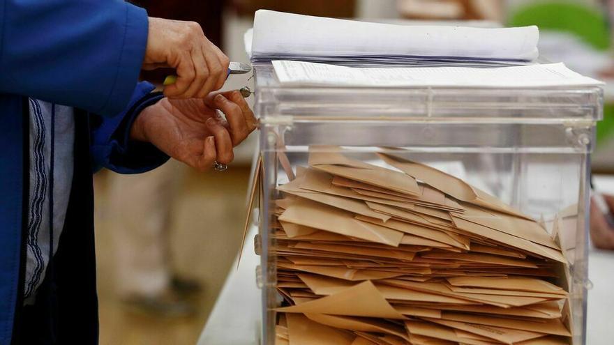 Una presidenta de mesa desprecinta una urna utilizada en las elecciones generales.