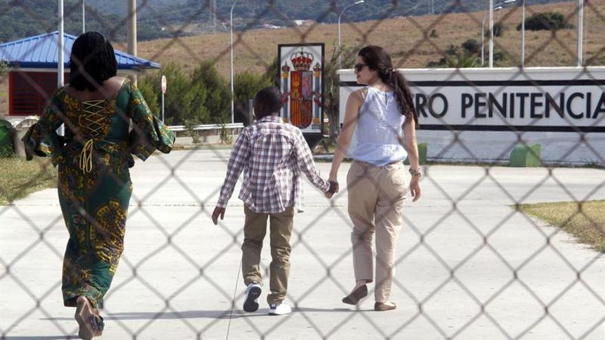 El pequeño Adou, con una asistenta social y seguido por su madre Lucie a su llegada al centro penitenciario de Algeciras donde ha sido puesto en libertad su padre. (EFE/J.RAGEL)
