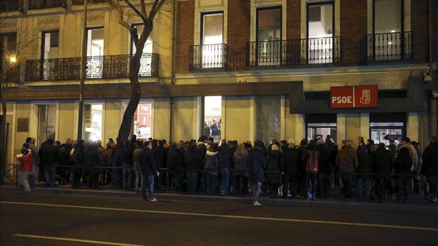Medio centenar de personas se manifiestan ante la sede del PSOE. / Efe