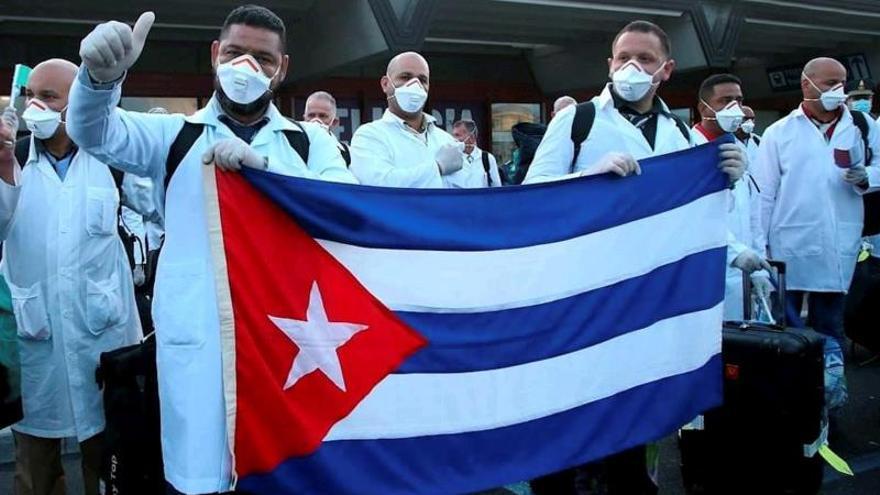 Fotografía cedida este domingo por la Casa Presidencial de Honduras que muestra a los integrantes de una brigada médica de Cuba mientras saludan tras llegar al Aeropuerto Internacional Ramón Villeda Morales de San Pedro Sula (Honduras).