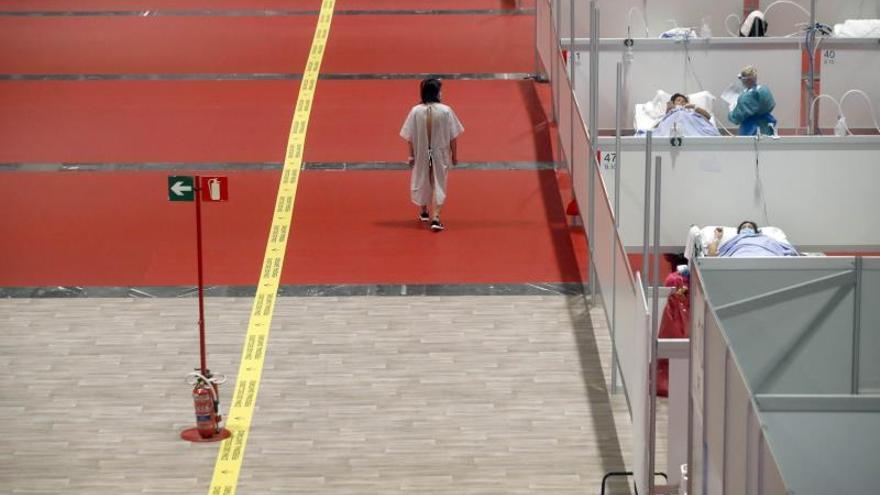 Un paciente camina por las instalaciones en el pabellón 9 del centro de exposiciones Ifema, reconvertido en hospital temporal, durante la puesta en marcha de las primeras UCIs, ayer, en Madrid.