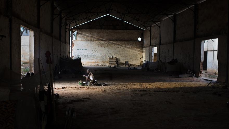 """Ivone Pounendji, viuda y madre de siete hijos, de la aldea de Yamalé (PK30), camino de Bakala. Ella huyó al monte con sus hijos, entre los cuales su hija de 5 años está herida en un pie. """"Pasamos dos años en el campo de desplazados internos de Notre Dame de la Victoire en Bambari y huimos por segunda vez en 2016. Hemos estado en esta antigua fábrica de algodón durante los últimos 18 meses"""". Ella sobrevive cocinando para los granjeros."""
