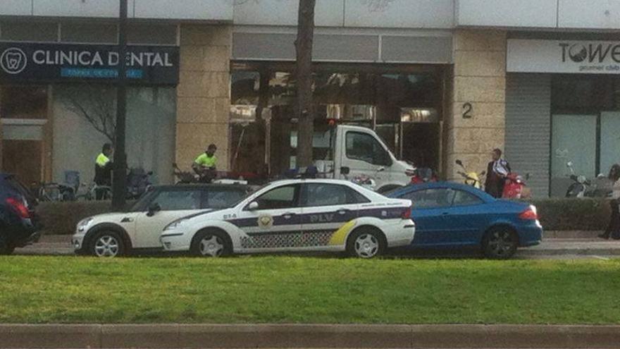 Una grúa retira un coche en Valencia en presencia de la Policía Local