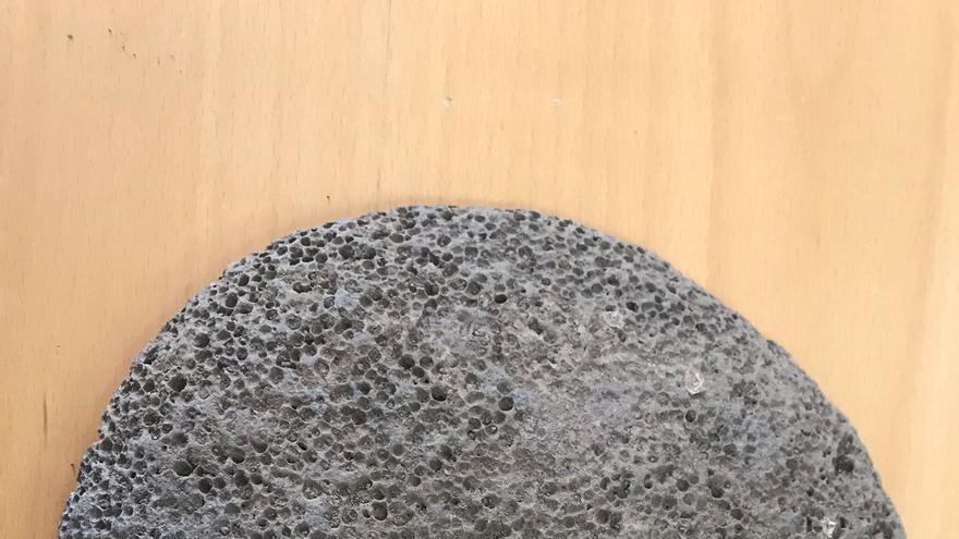Muela superior de un molino de mano Benahoarita.Tiene apenas 14 centímetros de anchura y por la cara plana presenta evidentes huellas de su uso cotidiano,