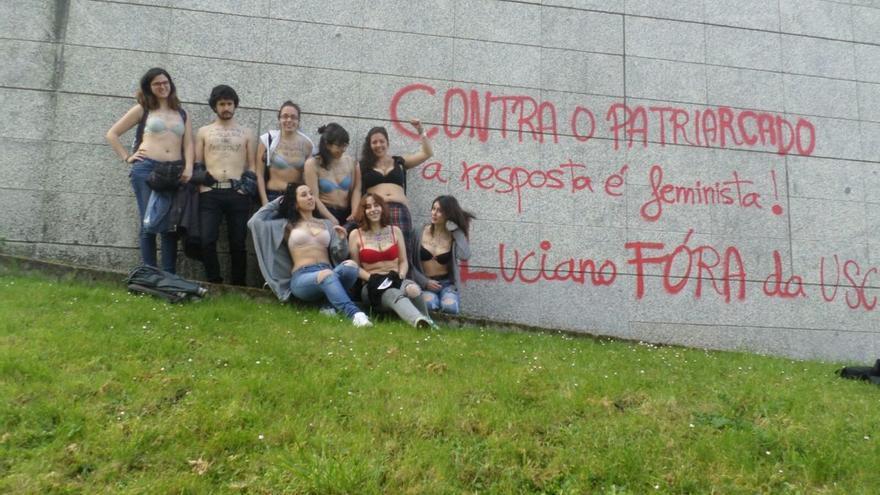 Las estudiantes que participaron en la acción posan ante una pintada que pide la expulsión del docente