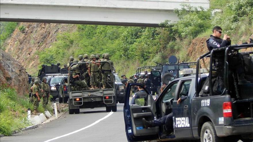 Agentes federales y soldados del Ejército mexicano resguardan una carretera.