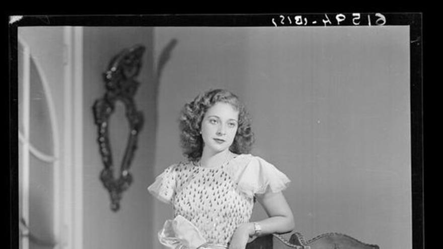 Retrato de mujer con vestido largo apoyada en un biombo. Estudio Coyne.