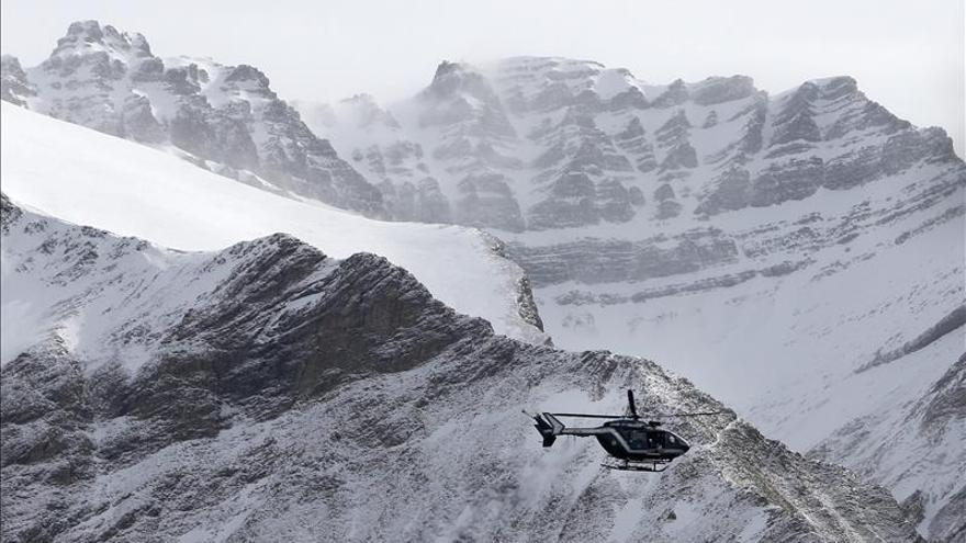 Un helicóptero de los servicios de rescate vuela sobre los restos del avión siniestrado
